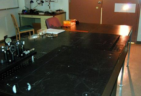 In this image, the thin beam of a filament laser is barely visible against the tabletop surface.
