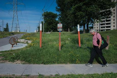 A resident walks past signs indicating Enbridge's 38-year-old Line 9 pipeline. The pipeline currently carries conventional oil from Montreal to southern Ontario but is slated to be reversed to transport tarsands bitumen and Bakken crude oil from the west to the east. Photo from Briarpatch Magazine